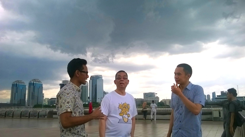 On the cup of the National Monument with Jason and his dad, Mr. Chin with dark clouds above Jakarta.