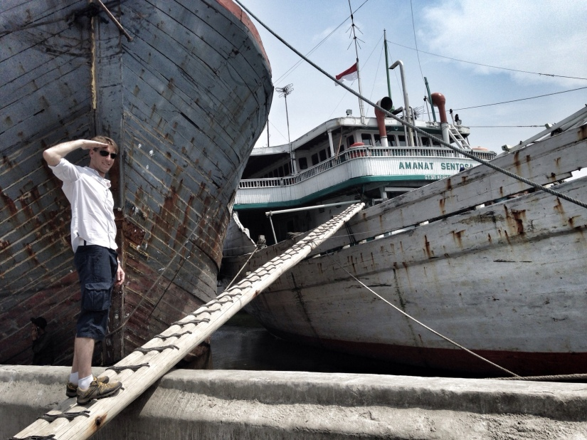 Geoffroy taking a fear factor challenge on a ladder to go to one of the boats in Sunda Kelapa