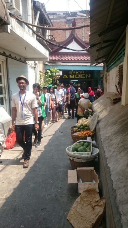 Walking on a narrow street and checking on the things sold on the side of the street.