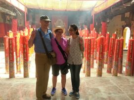 Gaye, her husband, and Tasya in front of giant candles in one of the oldest temples in Jakarta.